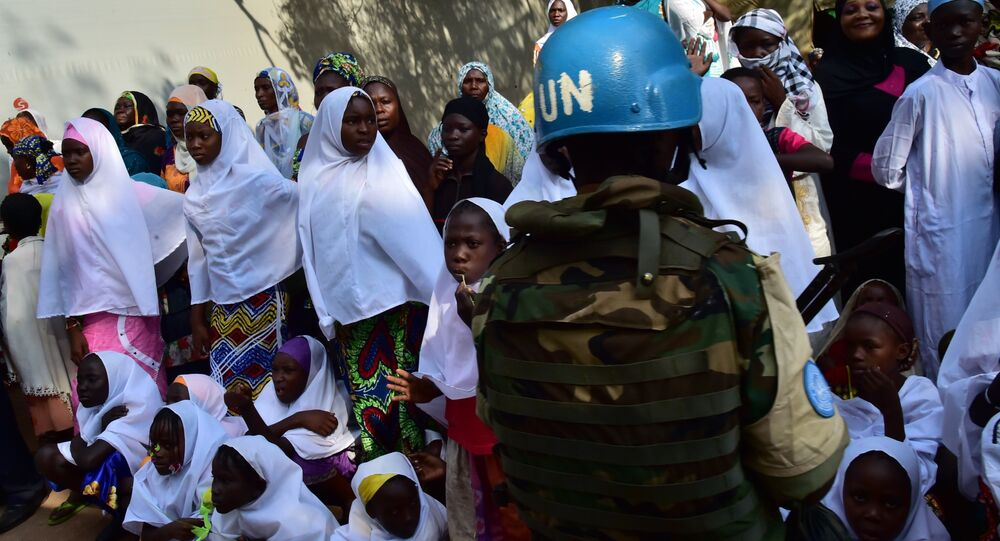A soldier of the United Nations (UN) stands guard next to girls and women at the Bangui Mosque, Central African Republic, on November 30, 2015.