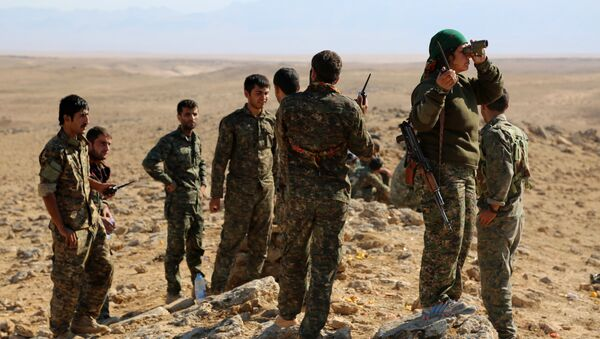 A group of coalition forces, which includes People's Protection Units (YPG) Women's Protection Units (YPJ), Sutoro militia, a pro-government Syriac Christian movement, and other forces, monitor the area in al-Hol in the Syrian Hasakeh province, some 650 kms northeast of Damascus, near the Iraqi border on November 2, 2015 - Sputnik International