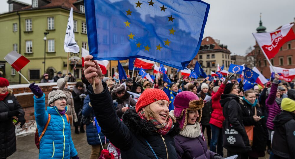 People wave European and Polish flags and sing the European anthem Ode to Joy as they take part in a flash mob to protest against a new media law in the center of Warsaw on January 9, 2016.