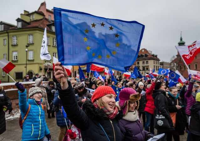 People wave European and Polish flags and sing the European anthem Ode to Joy as they take part in a flash mob to protest against a new media law in the center of Warsaw on January 9, 2016