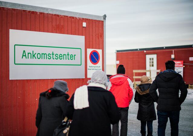 Refugees enter the arrival center for refugees near the town on Kirkenes, northern Norway, close to the Russian - Norwegian border on November 12, 2015.