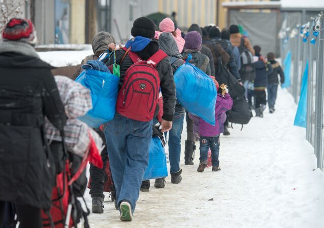 Refugees walk to a chartered train at the railway station of Passau, Germany, Jan. 5, 2016