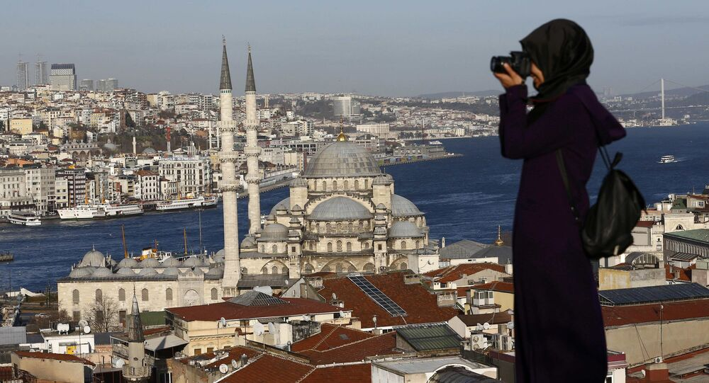 A woman takes photographs in front of the New Mosque by the Bosphorus strait in Istanbul, Turkey January 12, 2016