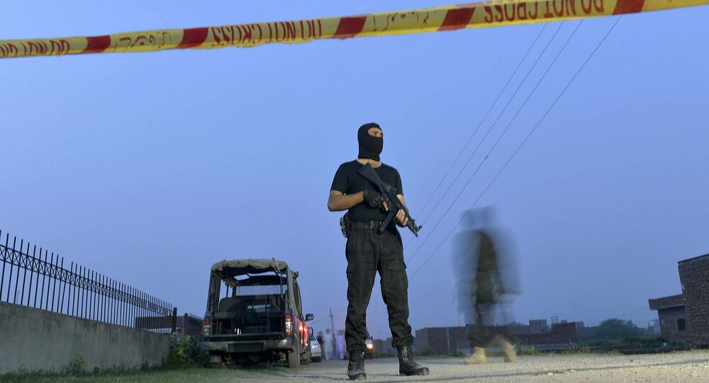 A Pakistani police commando stands alert at a cordon near a house on the outskirts of Lahore on June 29, 2015