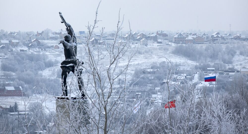 A monument to Red Army soldiers killed in action against Nazi Germany troops during World War II during the counteroffensive in 1941, at left, and Red and Russian national flags, right, are seen over houses covered with frost in the village of Peremilovo in Moscow region, Russia