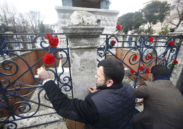 Men place flowers at the Obelisk of Theodosius, the scene of the suicide bomb attack, at Sultanahmet square in Istanbul, Turkey January 13, 2016.