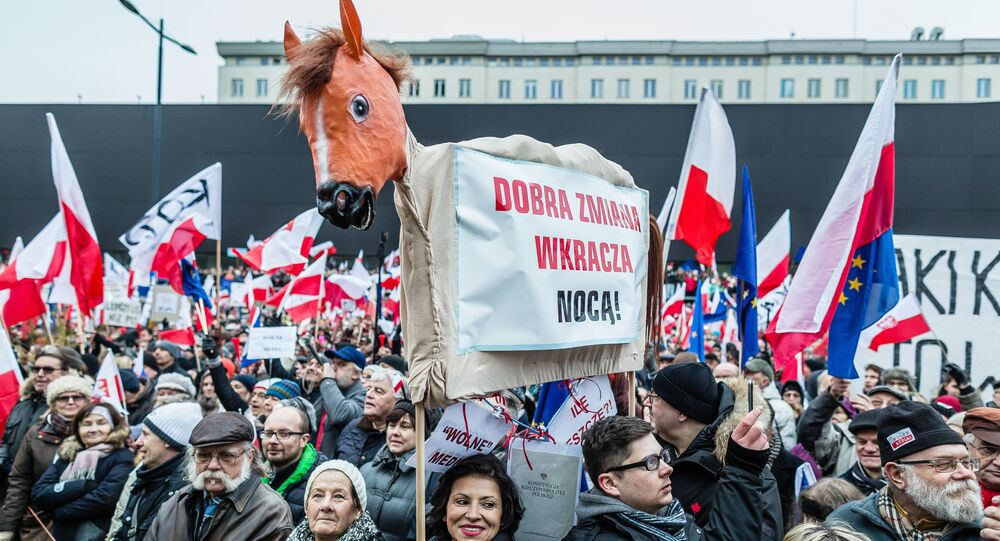 People wave European and Polish flags as they take part in a protest against a new media law in the center of Warsaw on January 9, 2016.