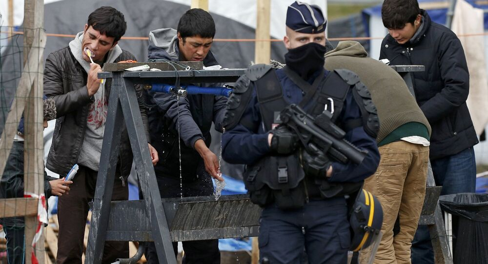 A French riot police officer (CRS) stands guard as migrants brush their teeth in a makeshift camp in what is known as the Jungle, a squalid sprawling camp in Calais, northern France, January 11, 2016.