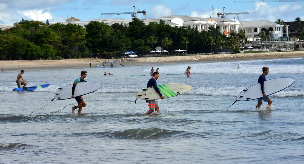 Foreign tourists hold surf boards as they wade into the waters off Kuta beach, Bali island