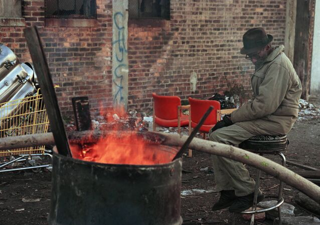 A homeless man sits by a barrel fire to keep warm near downtown Detroit. (File)
