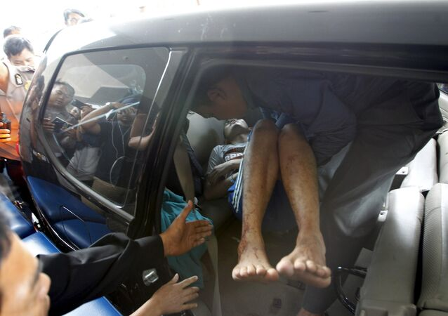 A man wounded in a gun and bomb attack in central Jakarta is helped from a car upon arrival at a hospital in Jakarta January 14, 2016