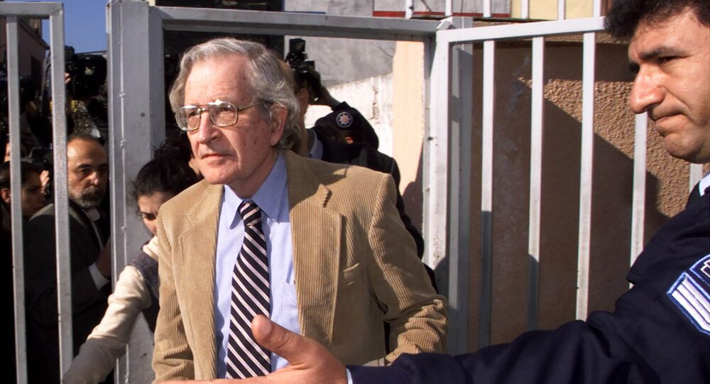 Noam Chomsky, the American linguist and political dissident, arrives at the State Security Court of Istanbul, Turkey, Wednesday Feb. 13, 2002, as a Turkish policemen , right, shows him the entrance. A Turkish court cleared the publisher of a book by Noam Chomsky which slams Turkey's human rights record and its treatment of the Kurdish minority.
