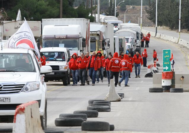 A convoy of aid from the Syrian Arab Red Crescent waits on the outskirts of besieged rebel-held Syrian town of Madaya