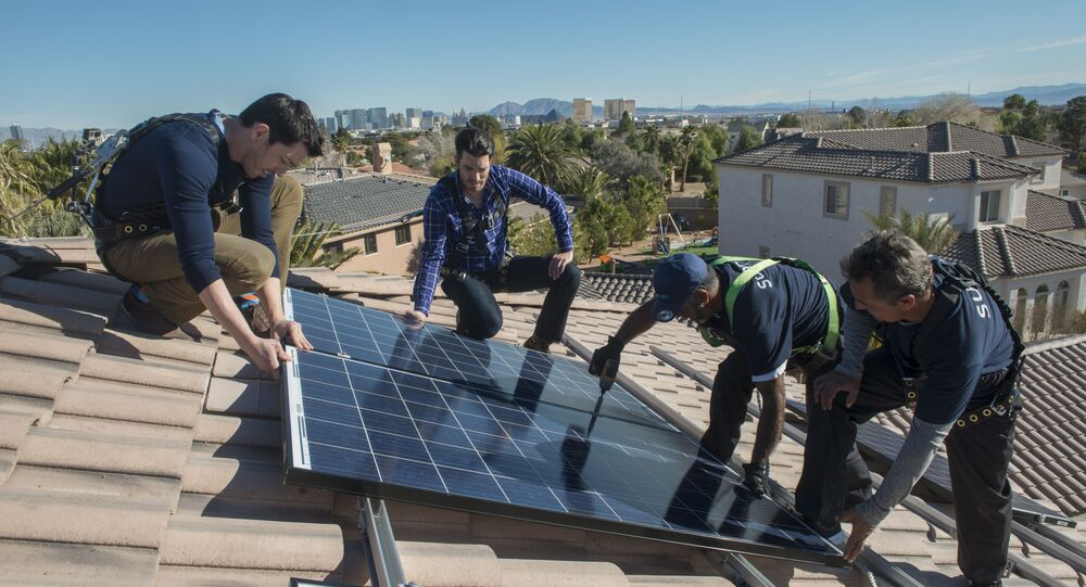 In this handout photograph provided by Sunrun, real estate experts install solar panels on a home in Las Vegas.