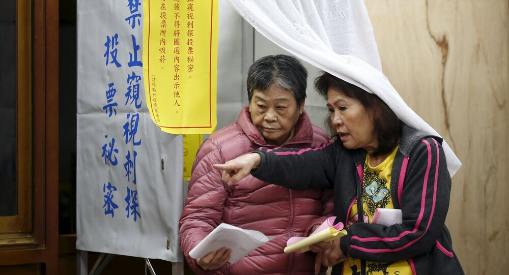 A voter casts her ballot at a polling station during general election in Taipei, Taiwan, January 16, 2016