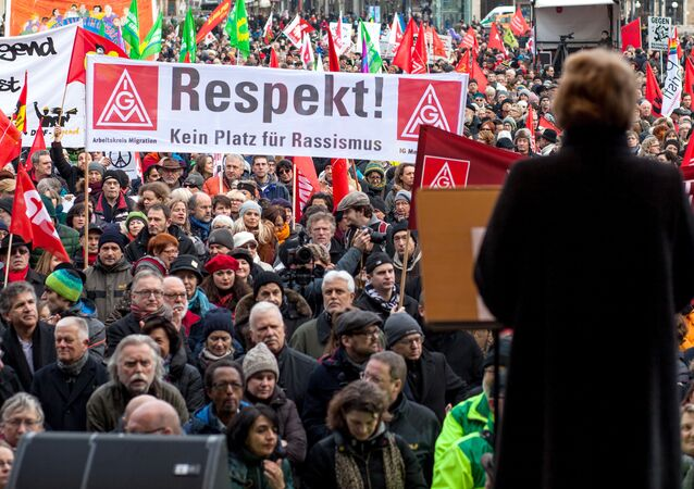 People gather at the center of Stuttgart, Germany during a rally to support refugees Saturday Jan. 16, 2016. Poster reads: Respect, No place for Racism.