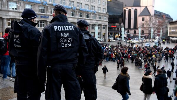 Policemen look on as refugees from Syria demonstrate against violence near the Cologne main train station in Cologne, western Germany on January 16, 2016 - Sputnik International
