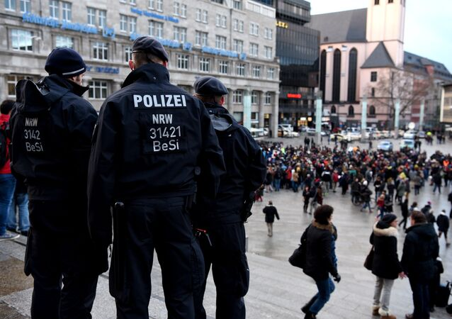 Policemen look on as refugees from Syria demonstrate against violence near the Cologne main train station in Cologne, western Germany on January 16, 2016.