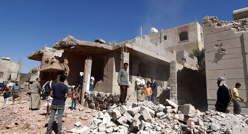 Yemeni men walk past a building, damaged during an air-strike by the Saudi-led coalition, in the capital Sanaa on November 29, 2015