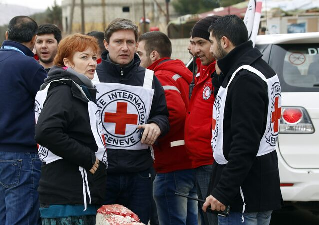 In this Monday, Jan. 11, 2016 photo, aid workers stand near a convoy of vehicles loaded with food and other supplies organized by the International Committee of the Red Cross, working alongside the Syrian Arab Red Crescent and the United Nations, makes it's way to the besieged town of Madaya, about 15 miles (24 kilometers) northwest of Damascus, Syria