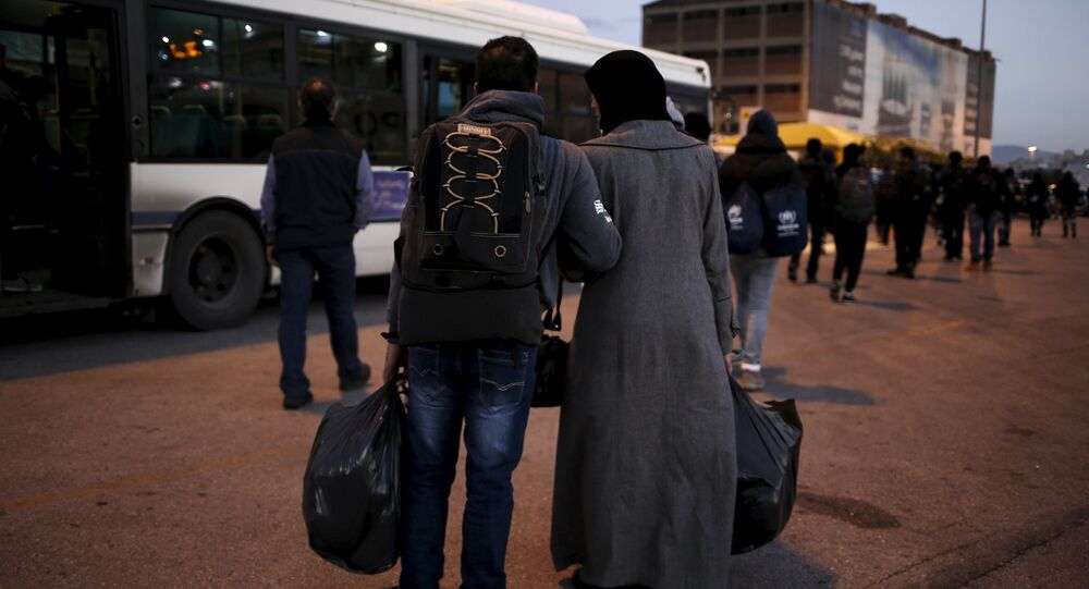 A Syrian refugee couple carry their belongings as refugees and migrants arrive aboard the passenger ferry Nissos Rodos at the port of Piraeus, near Athens, Greece, January 13, 2016