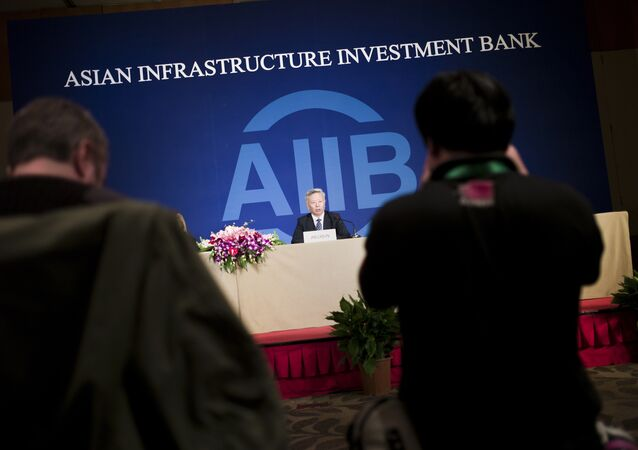 Jin Liqun (C), the first president of the Asian Infrastructure Investment Bank (AIIB), speaks to journalists during a press conference in Beijing on January 17, 2016