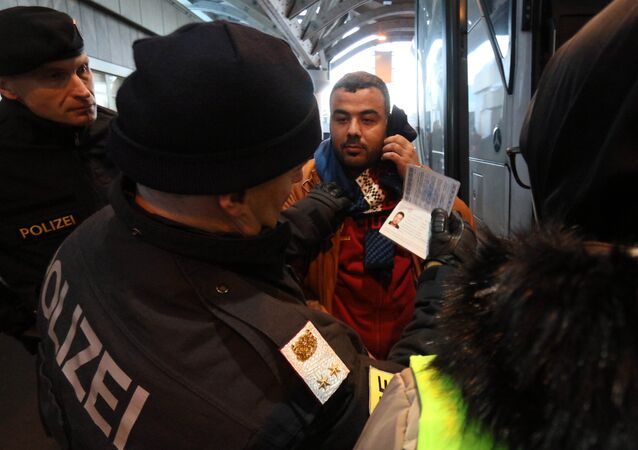 Austrian police officer check the identification documents of migrants before allowing them to get out a bus from Slovenia to cross the border from Slovenia into Austria, at a checkpoint at the Karawanks tunnel near Villach, Austria, Wednesday, Jan. 13, 2016
