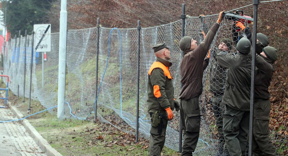 Austrian soldiers are building a fence to improve the procedure for arriving refugees at the border between Slovenian and Austria in Spielfeld, Austria, Tuesday, Dec. 8, 2015
