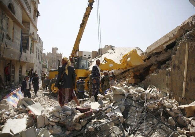 Policemen search for survivors at the site of a Saudi-led airstrike on the police headquarters in Sanaa, Yemen, Monday, Jan. 18, 2016