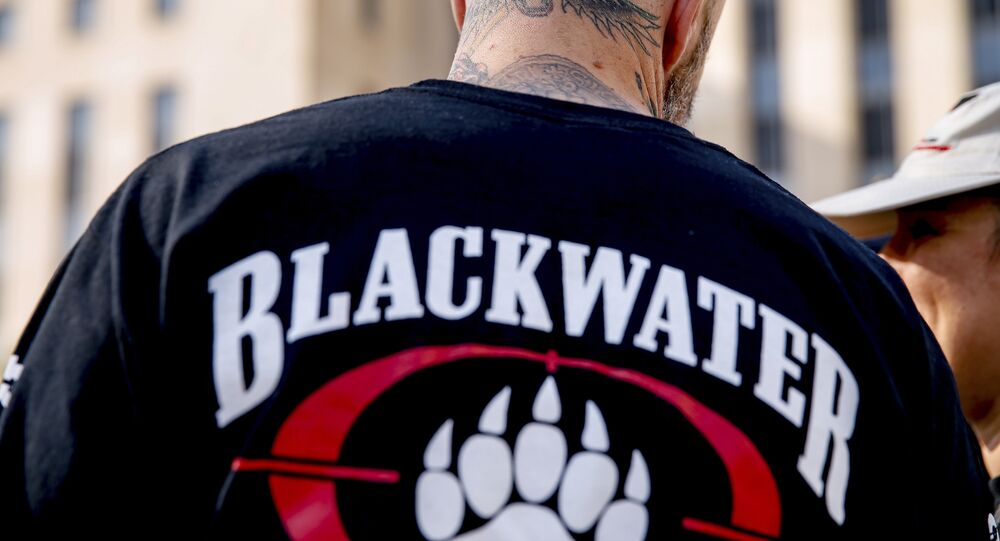 A former member of Blackwater joines family members, friends, and supporters of four former Blackwater security guards outside the federal court in Washington, Monday, April 13, 2015