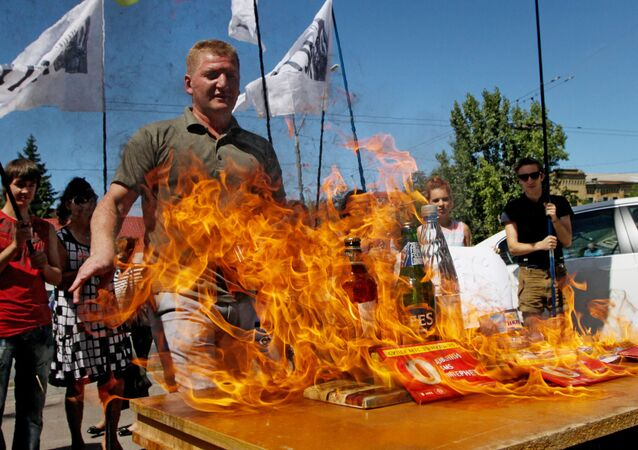 Participants of a protest rally against the halting of import of Ukrainian goods to Russia burn Russian goods in front of the Embassy of the Russian Federation in Kiev