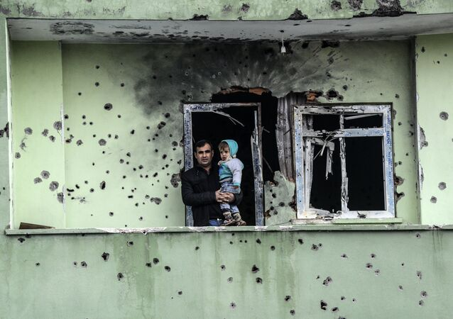 A man holding an infant stands on the balcony of a damaged house, after curfew ended in the southeastern Turkish town of Silopi on January 19, 2016