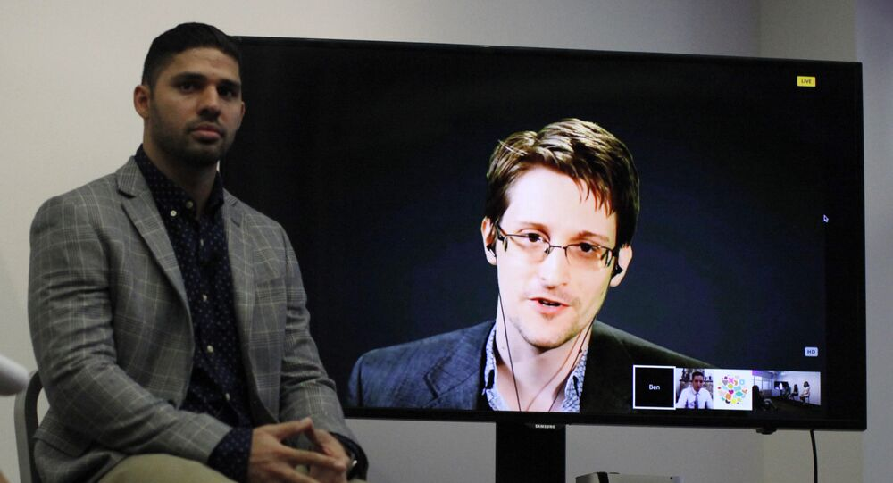 David Miranda (L) listens to American whistleblower Edward Snowden as he delivers remarks via video link from Moscow to attendees at a discussion regarding an International Treaty on the Right to Privacy, Protection Against Improper Surveillance and Protection of Whistleblowers in Manhattan, September 24, 2015 in New York