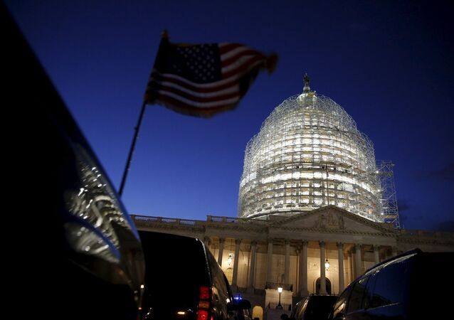 A U.S. flag on a vehicle flutters as the sun sets behind the U.S. Capitol dome in the hours before President Barack Obama delivers the State of the Union address to a joint session of Congress in Washington January 12, 2016