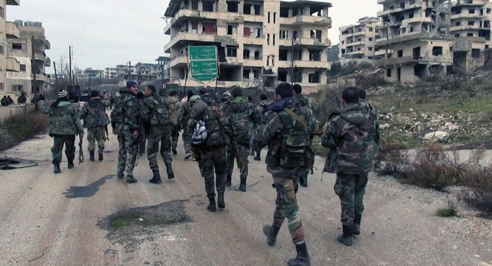Syrian government troops and allied militiamen walk inside the key town of Salma in Latakia province, Syria.