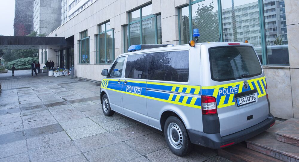 A police car stands in front of the initial reception center for asylum seekers in Halle/Saale, Germany, Friday, Oct. 16, 2015