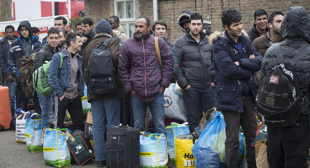 Refugees queue as they arrive at the vacation park Droomgaard in Kaatsheuvel, on January 6, 2016
