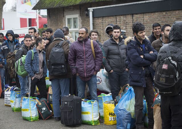 Refugees queue as they arrive at the vacation park Droomgaard in Kaatsheuvel, on January 6, 2016.