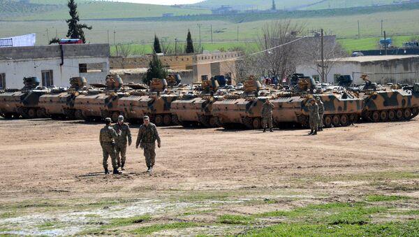 Turkish Army vehicles and tanks wait near the Syrian border in Suruc on February 23, 2015 - Sputnik International