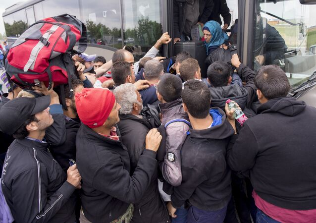 Migrants struggle to board a bus sent to pick them up on the closed highway A4 towards Vienna at the Austrian side of the border between Hungary and Austria on September 11, 2015 near Nickelsdorf, Austria