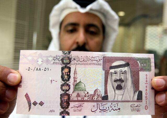 A Saudi banker displays the new one hundred riyal banknote bearing the portrait of Saudi King Abdullah bin Abdul Aziz al-Saud at a bank in Riyadh, 05 June 2007