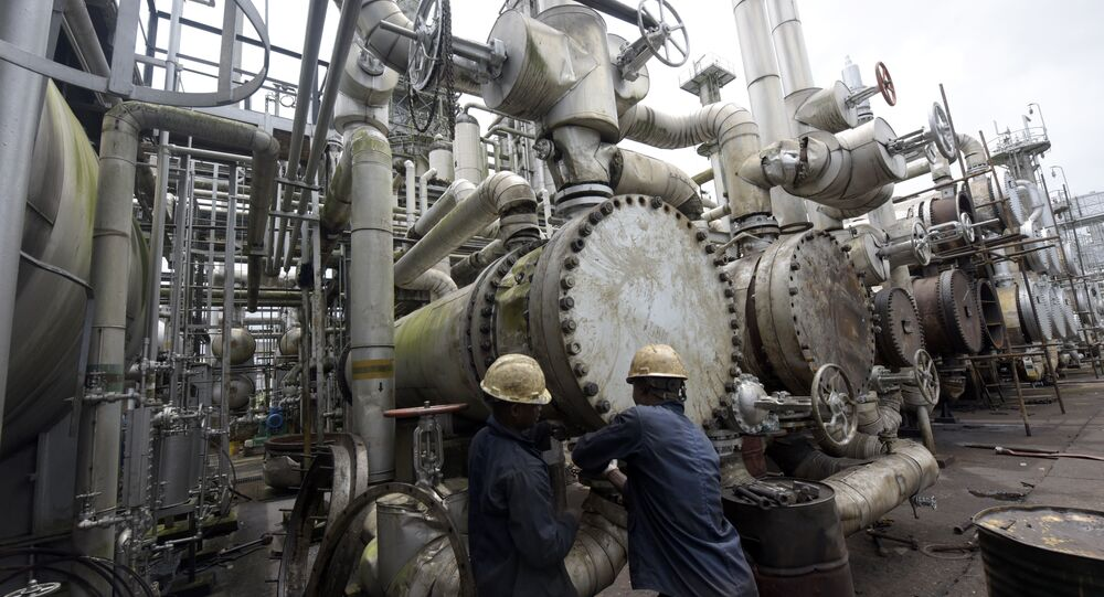 A picture taken on September 16, 2015 shows workers trying to tie a pipe of the first refinery in Nigeria, which was built in 1965 in oil rich Port Harcourt, Rivers State
