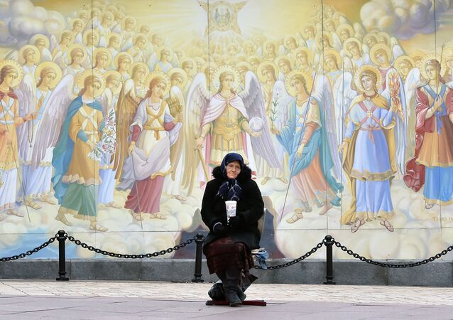 An elderly woman asks for alms outside the Saint Michael Golden-Domed Monastery in Kiev