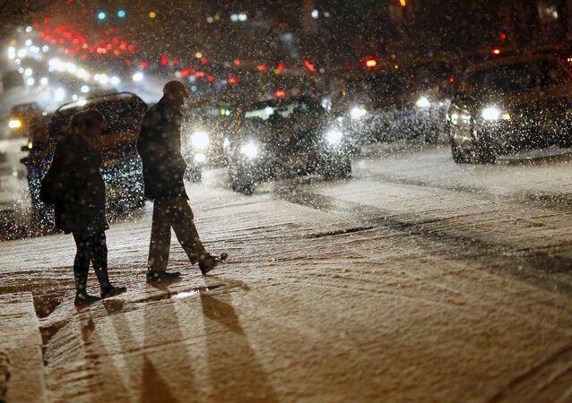 People cross a street as it snows in Washington