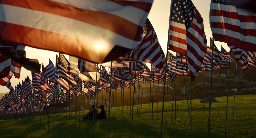 People sit amongst US national flags erected by students and staff from Pepperdine University