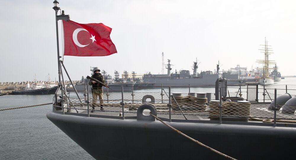 A Turkish marine serviceman stands on the deck of a Turkish navy TCG Turgutreis vessel