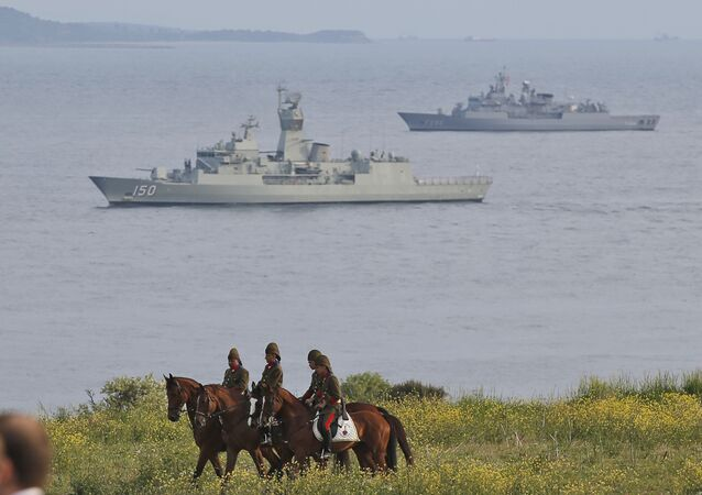 Backdropped by Turkish navy ships, mounted Turkish soldiers secure the area around the Helles Memorial in the Gallipoli peninsula