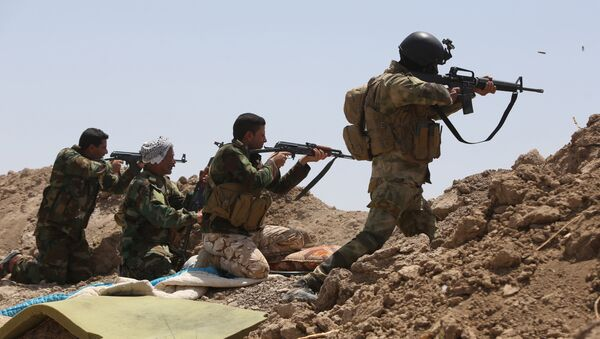 Iraqi soldiers and Shiite fighters from the popular committees hold a post as they fire towards Islamic State (IS) group positions in the Garma district of Anbar province west of the Iraqi capital Baghdad. (File) - Sputnik International