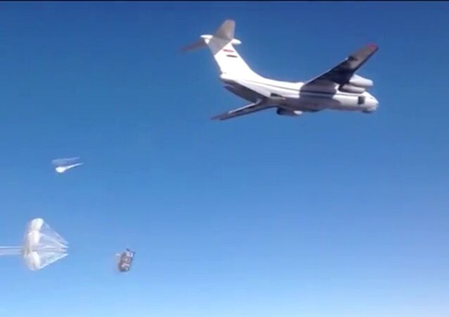 Syrian Air Force aircraft dropping humanitarian cargo on Russian parachute platforms in the area of Deir ez-Zor, Syria.