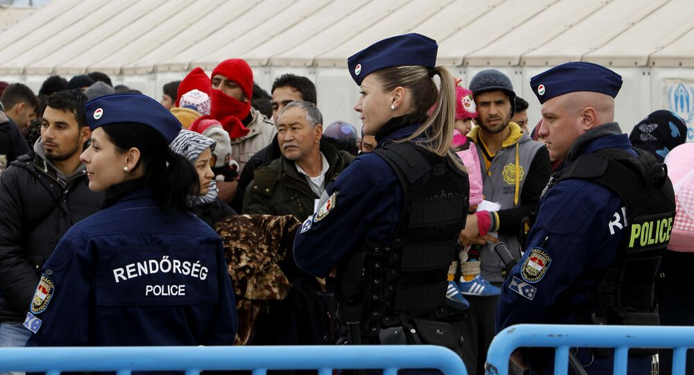 Hungarian police officers keep order as migrants wait to board a train towards Serbia.